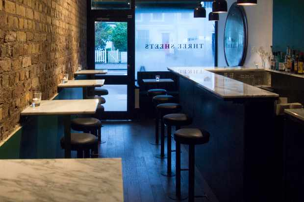 Marble tables in a narrow, brick-walled bar