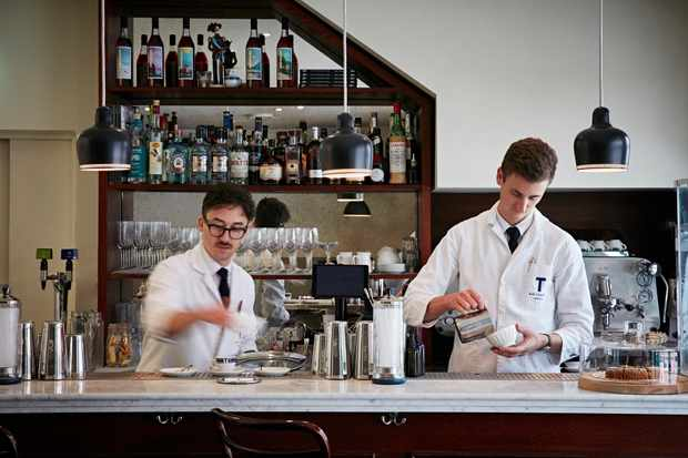 Two men in white lab coats mixing cocktails