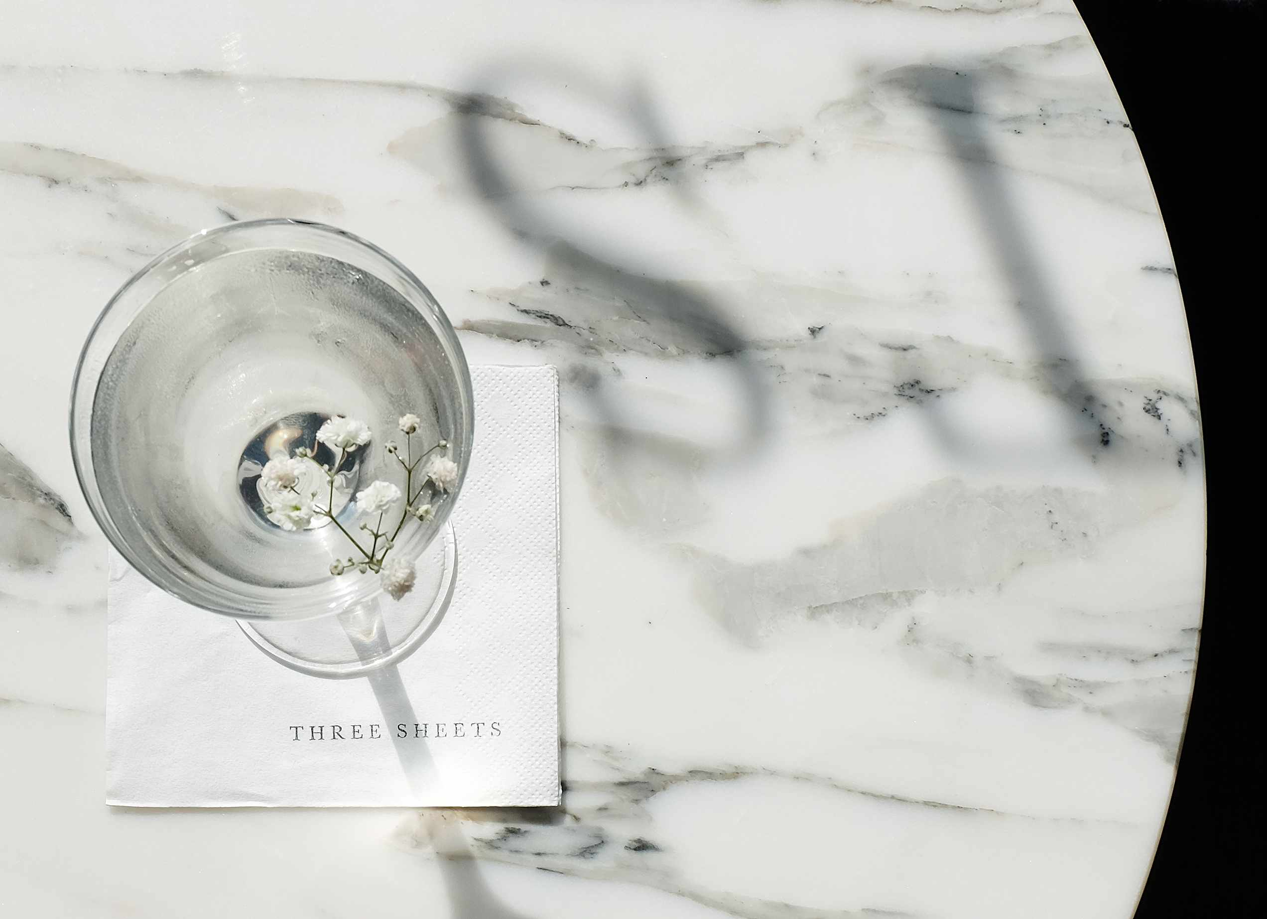 A coupette glass of clear liquid on a marble table at Three Sheets Dalston