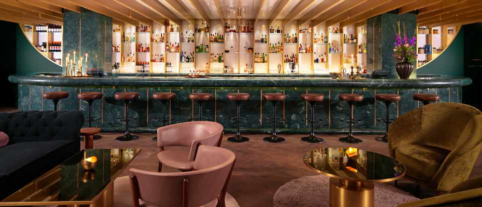 Dandelyan, London SE1: Hotel Bar Review. A bar with light pink chairs and a dark green counter