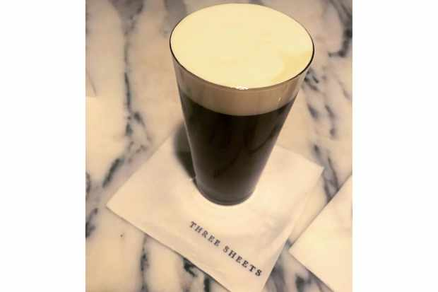 A glass of coffee coloured liquid with a creamy top, on a marble surface