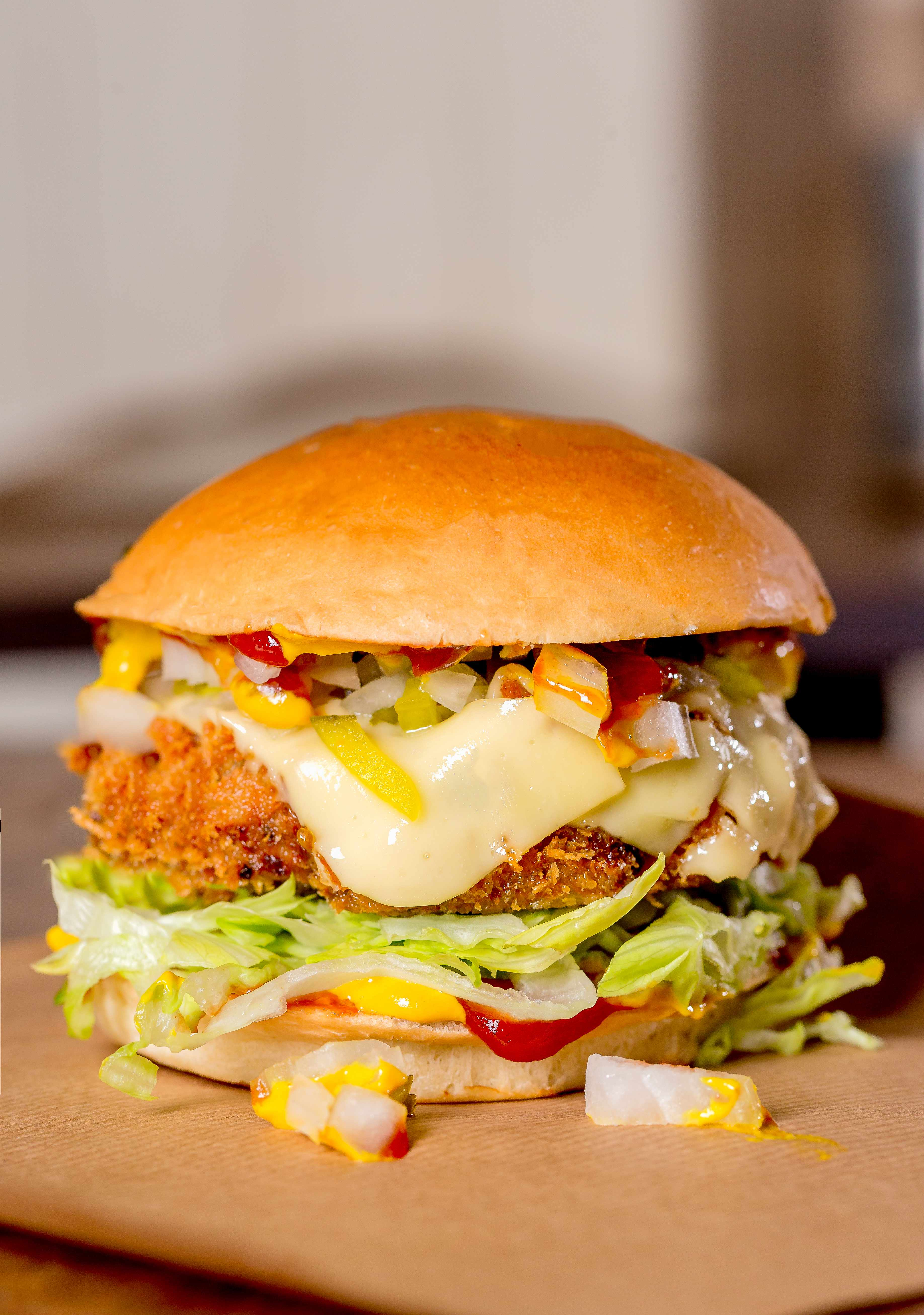 A burger with lettuce, cheese, a patty in a bun.