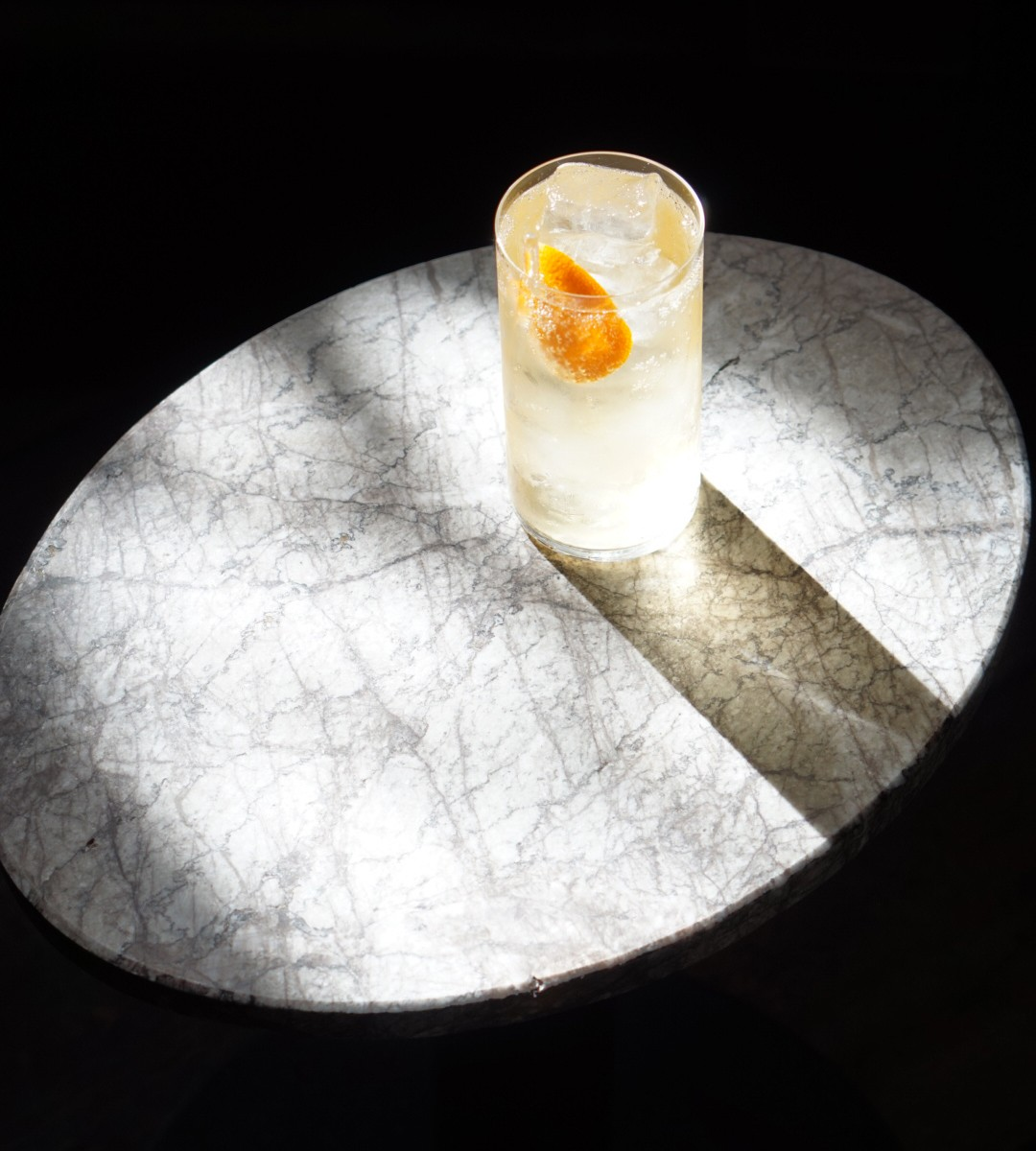 Sun shining on a marble table with a cocktail on it