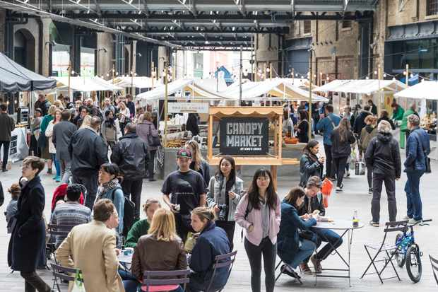 A large street food market in King's Cross, London. People are busy walking around and some are sat around tables eating food
