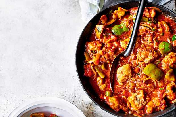 Chicken and Paprika Goulash Recipe served in a wide black pan on a pastel white table with a filled small white bowl