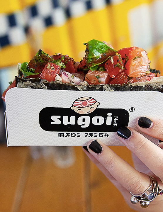 A woman holding up a seaweed taco filled with sushi tuna and salmon at Sugoi