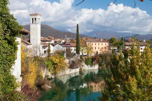 Cividale del Friuli. Beautiful Italian homes sitting high along the river with lots of bushes and greenery