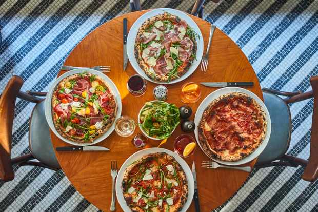 A mahogany table is topped with four pizzas and glasses of Aperol spritz at Soho House's Cecconi's Pizza Bar