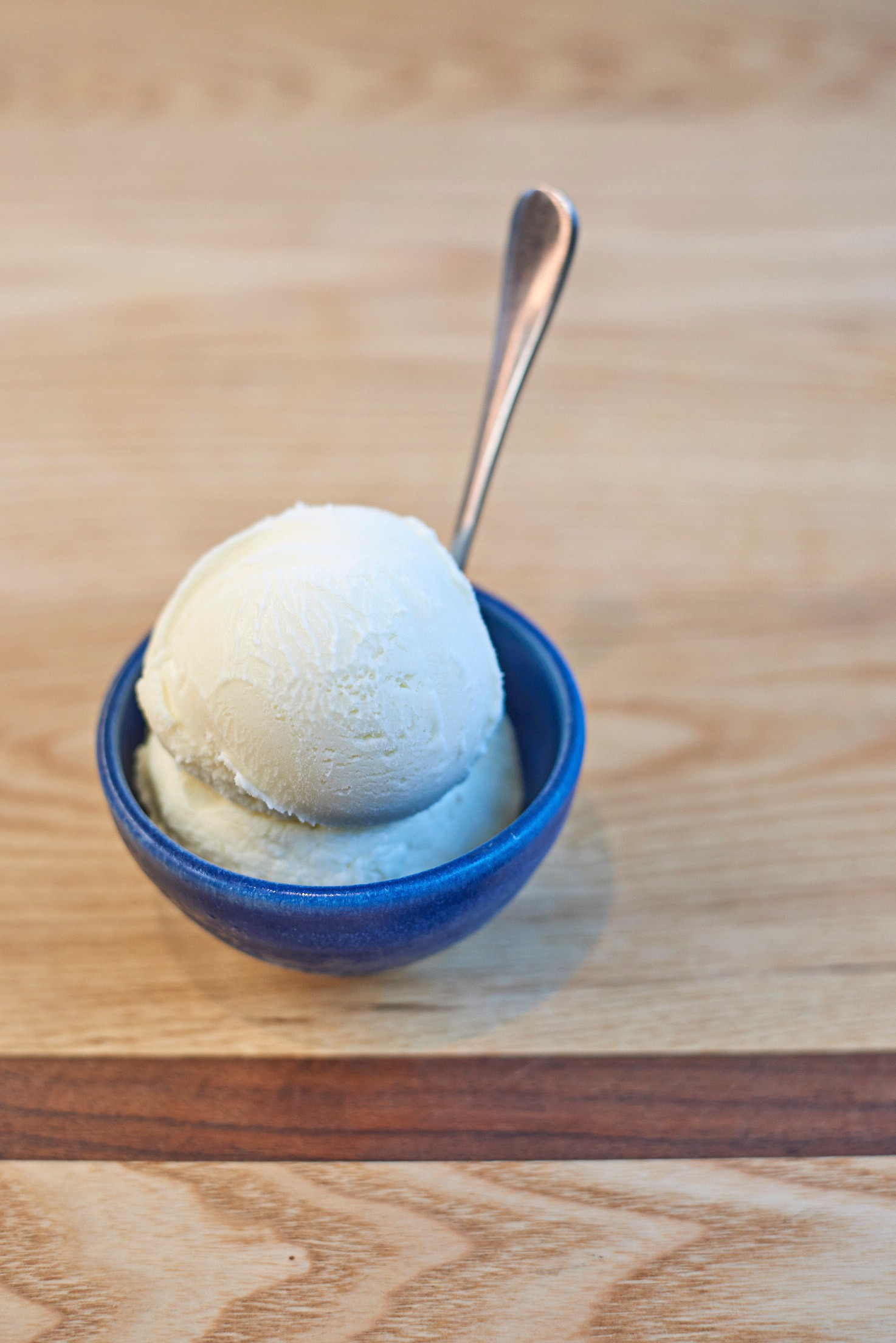 Black Pepper Ice Cream with Bay Leaves served in a very small blue bowl on a wooden table