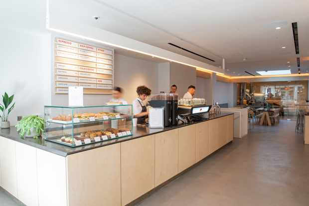 Interiors of Kiss the Hippo - a large pale wood counter with a coffee machine on top