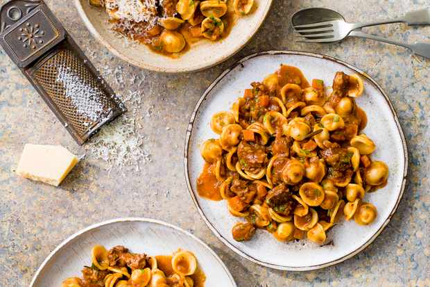 Goat Ragu Recipe with Orecchiette Pasta served in2 round pasta dishes with a high grating of parmesan