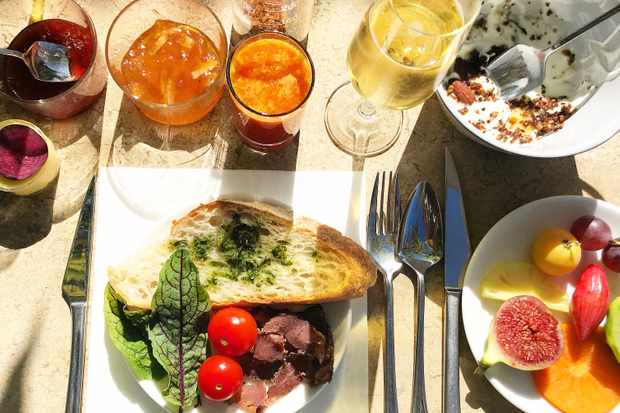 A breakfast spread with bread and pesto, a glass of champagne and orange juice