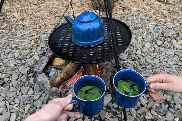 Mugs of mint tea with the kettle on the open fire at One Cat Farm, Wales