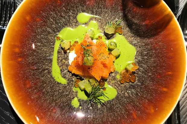 An orange plate with a fish tartare on it and vibrant green sauce