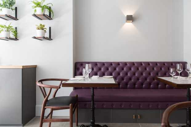 A purple leather sofa sits against a wall next to two marble tables at Stem, London