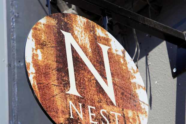 Rustic looking brown and round Nest sign hanging above the door outside the restaurant