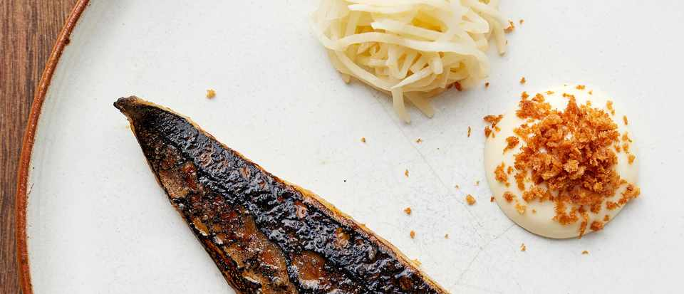 Mackerel Recipe with Celeriac and Lemon served on a off-white round plate on a dark brown wooden table