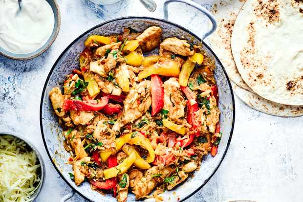 Chicken Fajitas served in a blue enamel dish with onions and peppers. Wraps, cheese, soured cream and guacamole surrounding the main dish