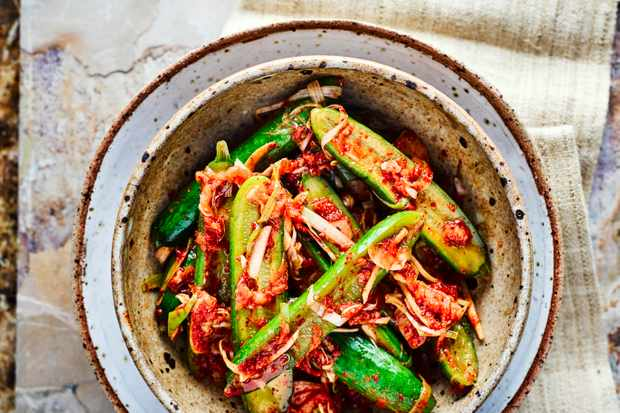 Cucumber Kimchi sliced in half with kimchi sprinkled on top, served in a deep speckled blue and grey bowl