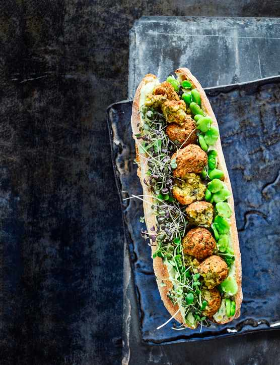 Falafel with Avocado Hummus Recipe and Broad Beans served in a crispy white baguette on a dark blue tray and table