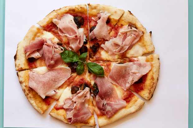 A pizza topped with tomatoes, fior di latte cheese, ham, mushrooms and basil