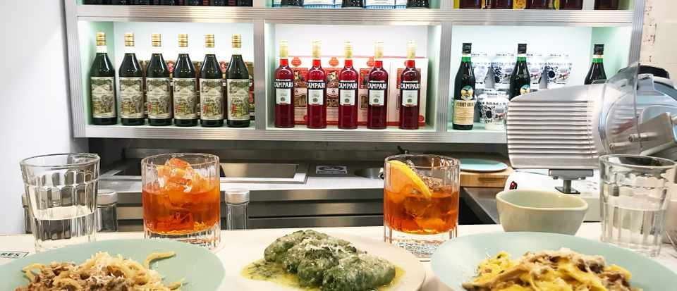 The plates of pasta at Lina Stores with shelves of bottles in the background