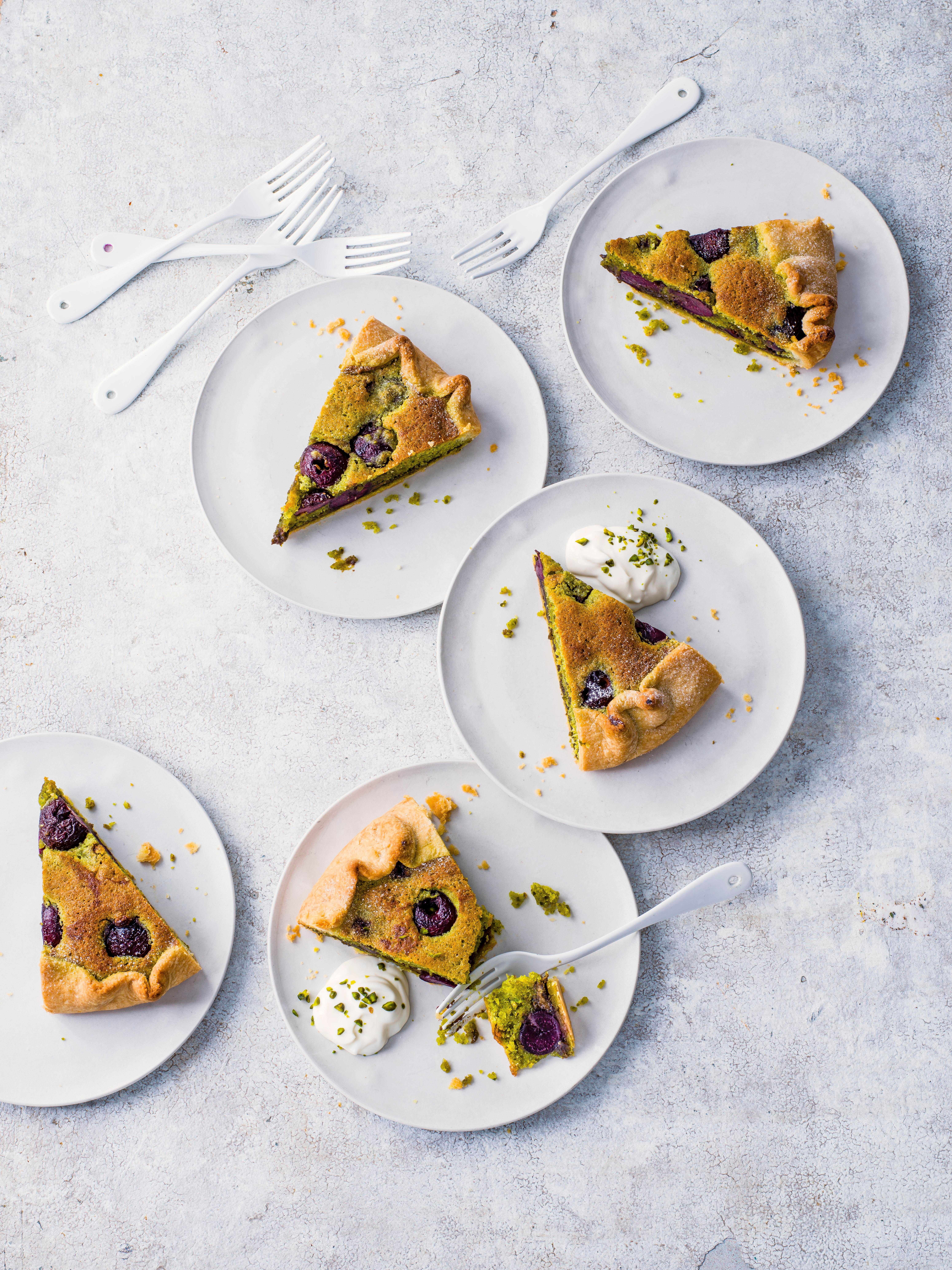 Bakewell Tart with Cherries and Pistachio galette cut up into triangles and served on round white plates on a rustic white table