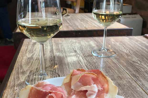 Proscuitto di Cormons with 2 glasses of white wine on a wooden table