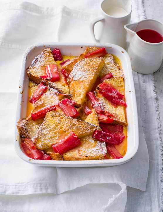 Vibrant Rhubarb and Custard Bread and Butter Pudding served in a rectangle white dish on a grey wooden table