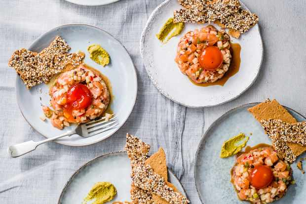 Salmon Tartare Recipe with Cured Egg Yolk and rice crackers, served on 6 get and white plates