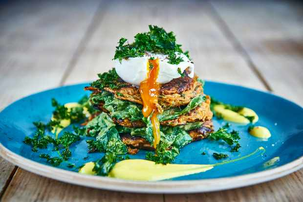 A blue plate topped with sweet potato and feta fritters, kale and a poached egg that the yolk is running out of