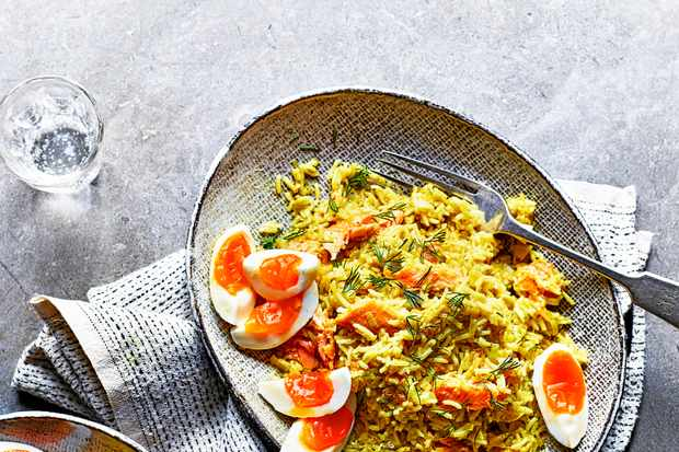 Smoked Trout Kedgeree with Leeks on a grey oval plate served with boiled eggs sliced into quarters