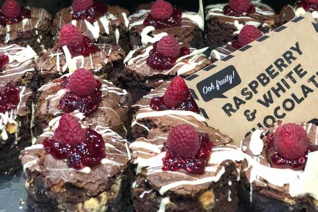 A tray of raspberry and white chocolate brownies, drizzled with white chocolate