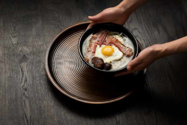 A bowl of udon noddles with bacon, fried egg and mushrooms at Koya, London