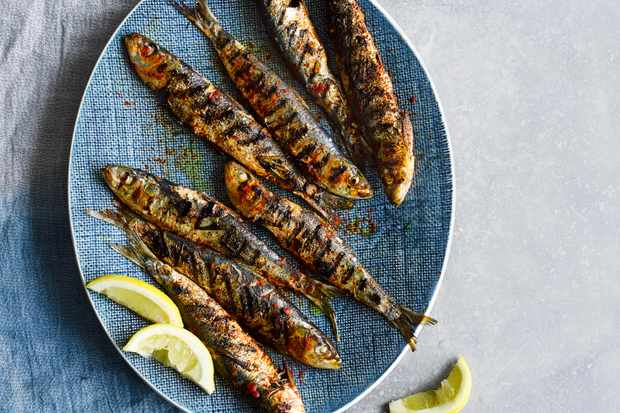 Grilled Portuguese Sardines served on an oval blue plate