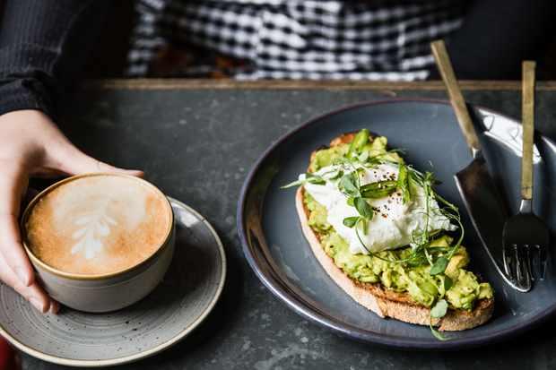 Avocado on toast and a coffee on a slate table