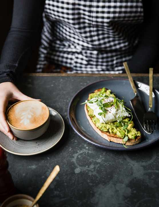 Avocado on toast and a coffee on a slate table