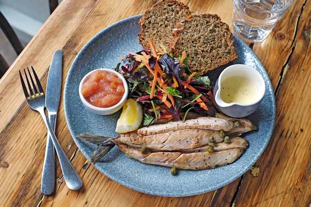 A blue plate with two pieces of bread, mackerel fillets and a salad