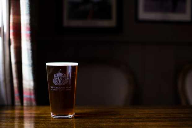 A pint of ale is sat on a dark wooden table against a dark background at the Duncombe Arms pub