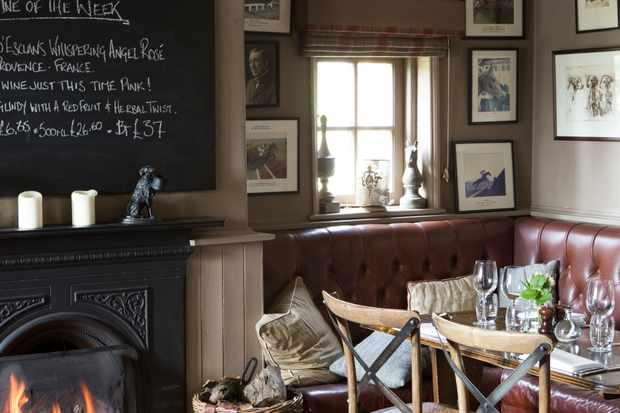 An open log fire is burning in the Duncombe Arms pub. There are red leather seats surrounding a wooden table and walls are covered in old pictures. A blackboard hangs on the wall listing the menu