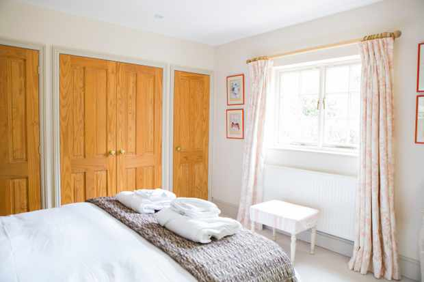 A white wall room has watercolour pictures hanging on the walls and gingham curtains hanging in the window. There is a double bed laid with white linen, a dark grey blanket and towels left on the bed