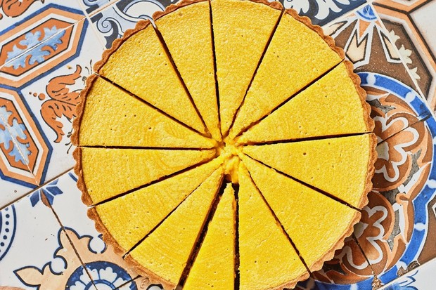 A vibrant yellow tart cut into equal slices set against a tiled background
