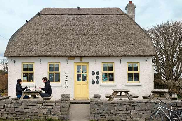 A thatched white house with a yellow door