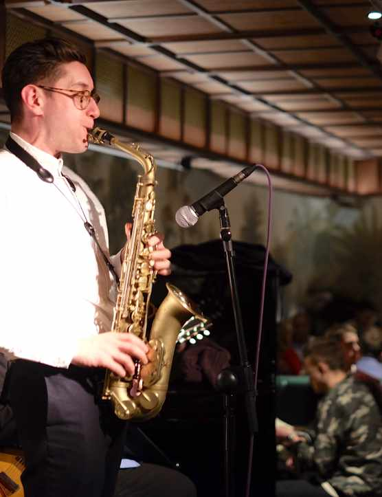 A man in a white shirt playing a saxophone with people watching