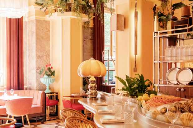 A bar in a peach coloured room with huge columns and plants hanging down