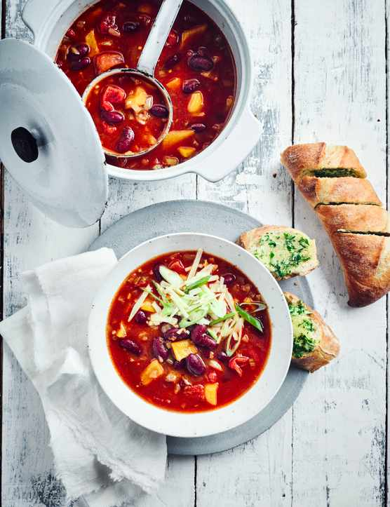 Chilli Soup Recipe served with garlic bread in a white bowl topped with chopped spring onions