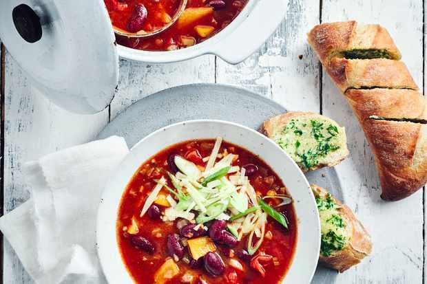 Zuppa di peperoncino Ricetta servita con pane all'aglio in una ciotola bianca condita con cipolline tritate