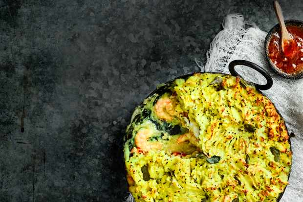 Indian Fish Pie Recipe served in a black round oven proof dish with a small dish of mango chutney on the side