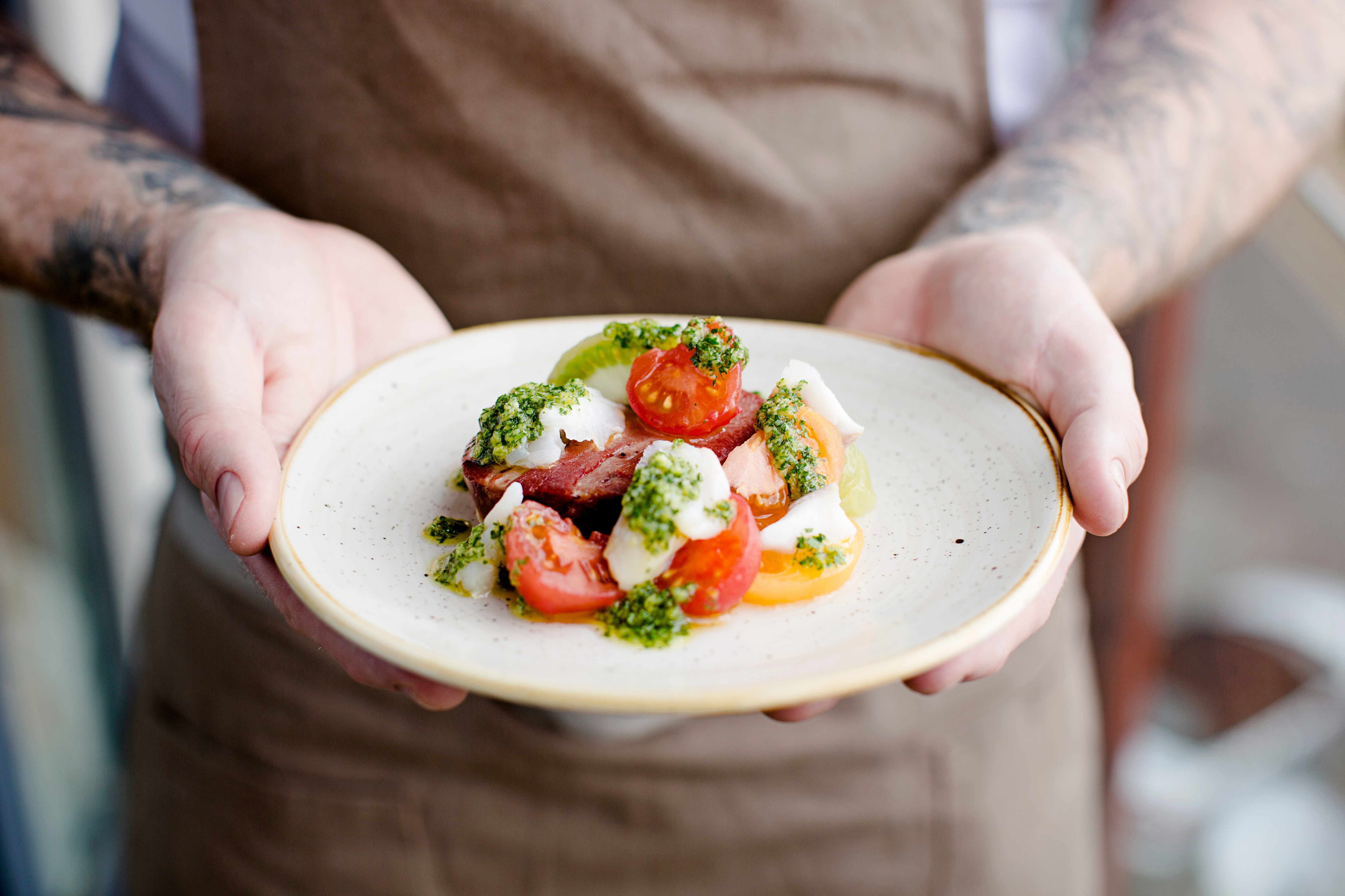 Ox tongue, salt cod, tomatoes, gremolata served on a white round plate