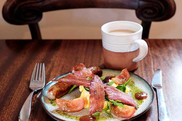A plate of bacon and a mug of tea on a wooden table